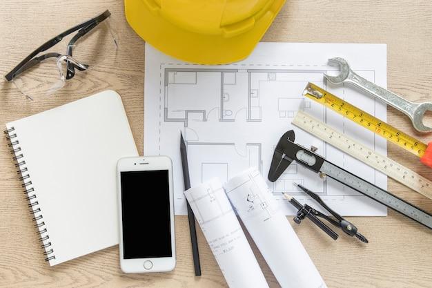 Smartphone e ferramentas de construção perto de projecto Foto gratuita