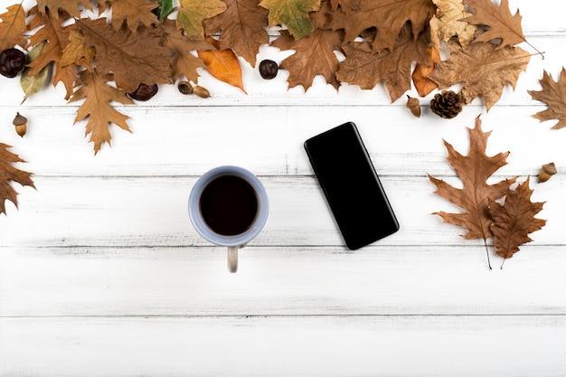 Smartphone e xícara de café no fundo de folhas de madeira Foto gratuita