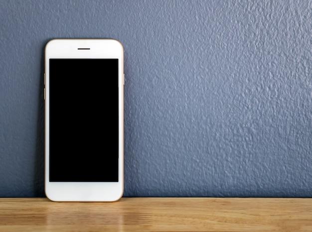 Smartphone encostado na parede cinza Foto Premium