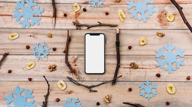 Smartphone entre galhos e flocos de neve decorativos Foto gratuita
