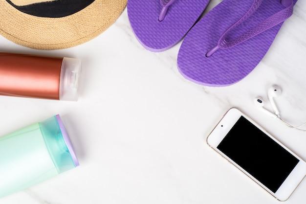 Smartphone, flip-flops, protetor solar e chapéu. Foto Premium
