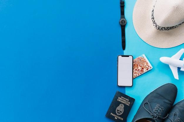 Smartphone; mapa; passaporte; avião de brinquedo; sapatos; relógio de pulso e chapéu em fundo duplo com espaço para escrever texto Foto gratuita