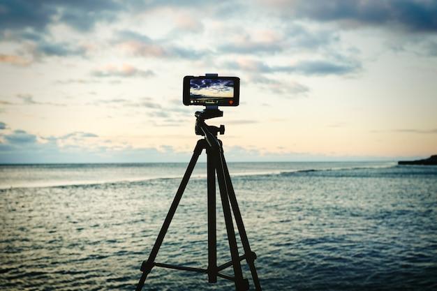 Smartphone no tripé capturando seascape nascer do sol. conceito de fotografia ou videografia móvel. Foto Premium