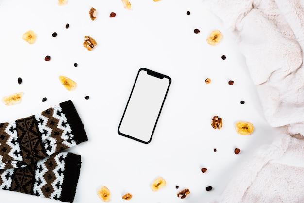 Smartphone perto de nozes e roupas Foto gratuita