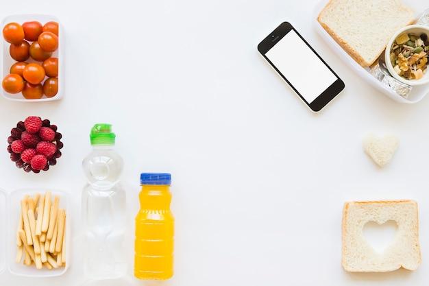 Smartphone perto de vários alimentos saudáveis Foto gratuita