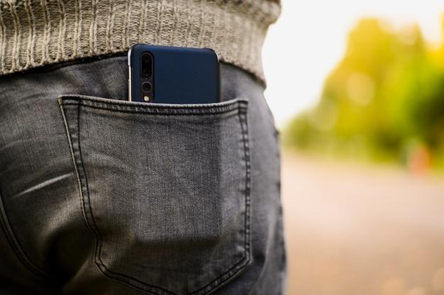 Smartphone preto no bolso de trás da calça jeans Foto gratuita