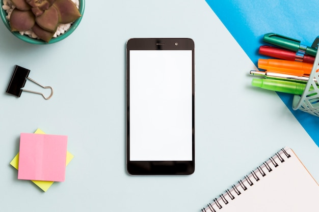 Smartphone rodeado por material de escritório Foto gratuita