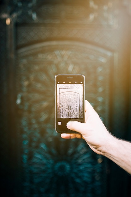 Smartphone tirando foto do padrão oriental Foto gratuita