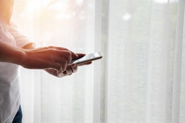 Smartphone tocante do homem de negócios, tabuleta no fundo branco das janelas da cortina. Foto Premium