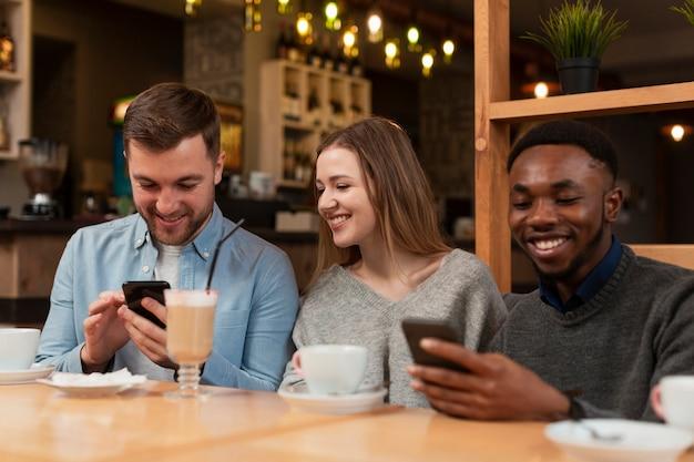 Smiley amigos usando telefones no restaurante Foto gratuita