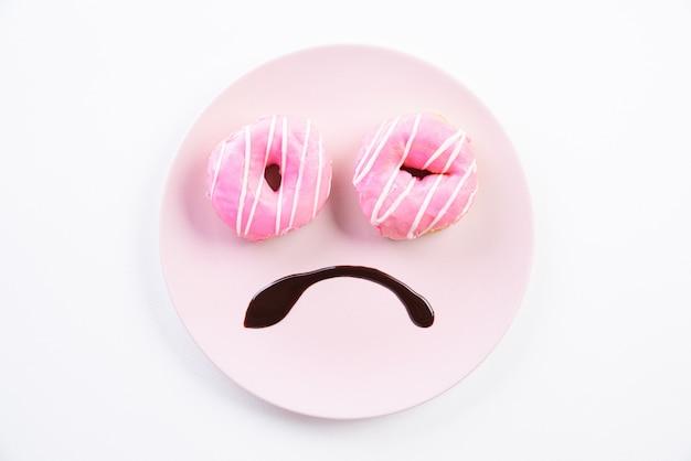 Smiley cara triste preocupado com excesso de peso feito no prato com donuts Foto Premium