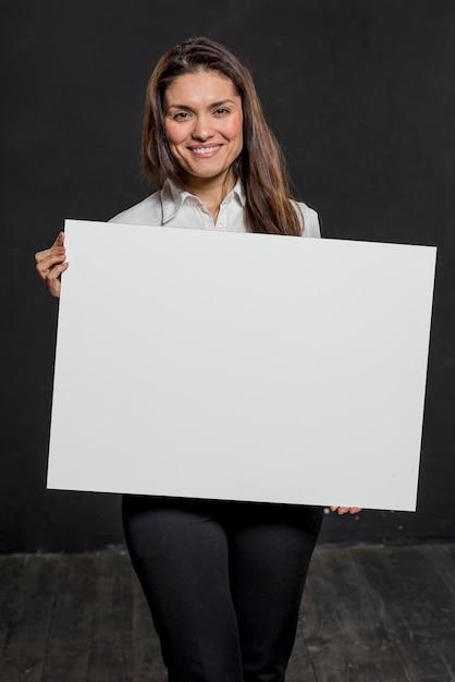Smiley feminino segurando a folha de papel em branco Foto gratuita