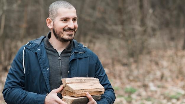 Smiley homem carregando madeira Foto gratuita