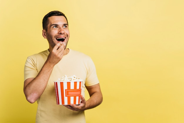 Smiley homem comendo pipoca com espaço de cópia Foto gratuita