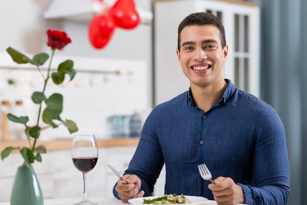 Smiley homem jantando no dia dos namorados Foto gratuita