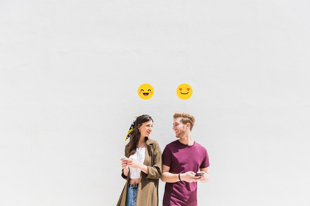 Smiley icon over smiling jovem casal usando smartphone Foto gratuita