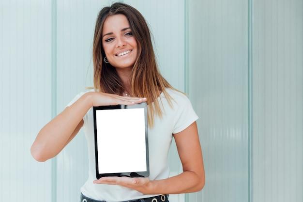Smiley jovem garota segurando o tablet Foto gratuita