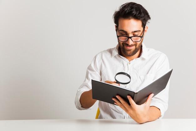 Smiley jovem lendo com lupa Foto gratuita
