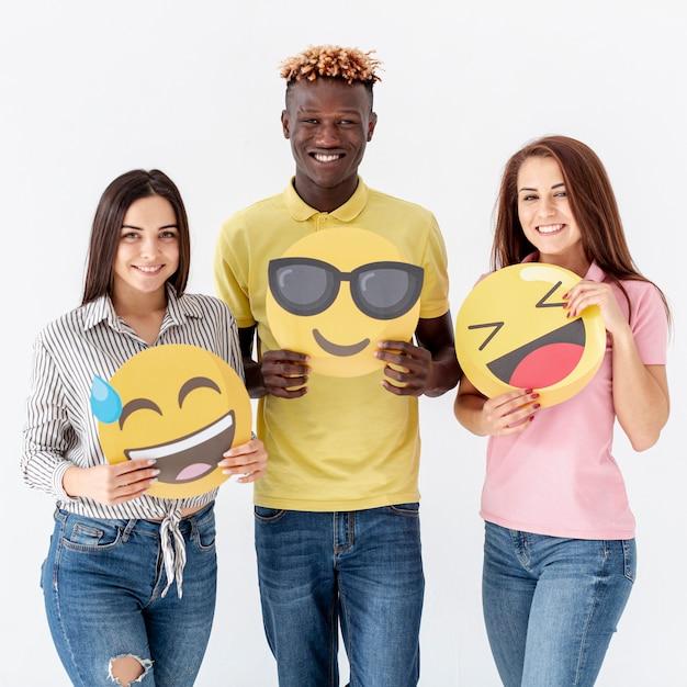Smiley jovens amigos segurando emoji Foto gratuita