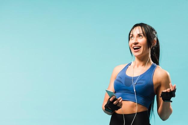 Smiley mulher atlética curtindo música em fones de ouvido Foto gratuita