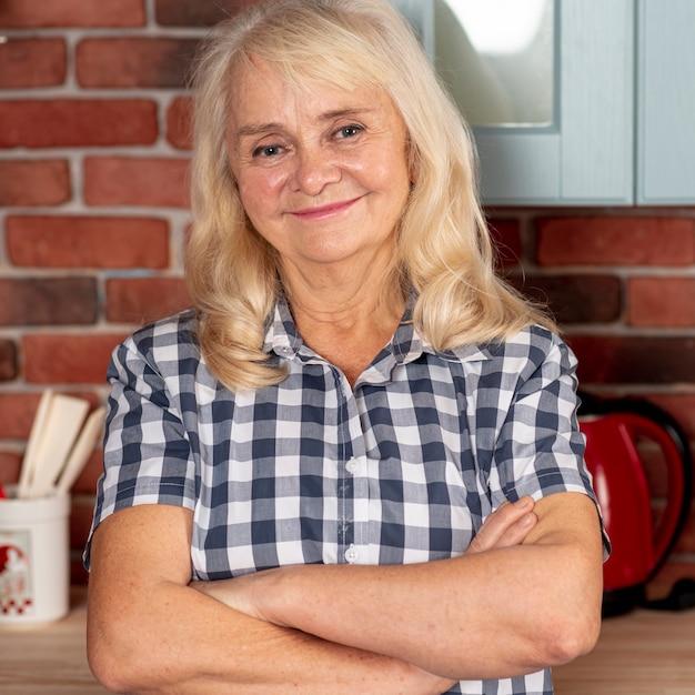 Smiley mulher idosa em pé na cozinha Foto gratuita