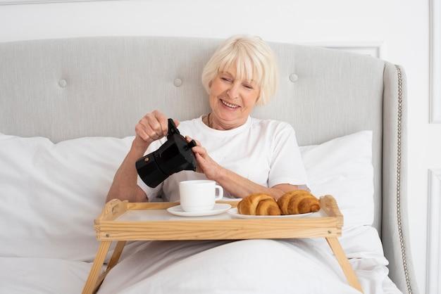 Smiley mulher idosa segurando chaleira no quarto Foto gratuita