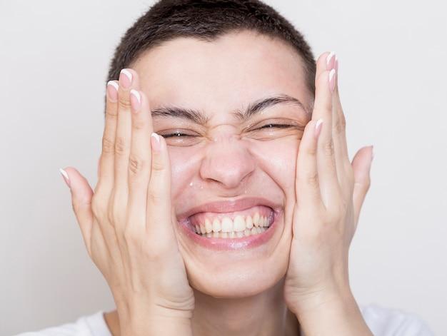 Smiley mulher limpando o rosto close-up Foto gratuita