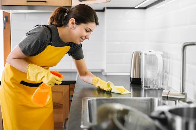 Smiley mulher limpeza de cozinha Foto Premium