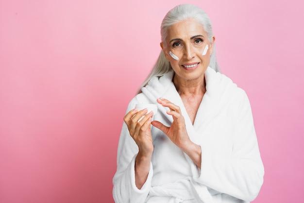 Smiley mulher sênior aplicar creme hidratante Foto gratuita
