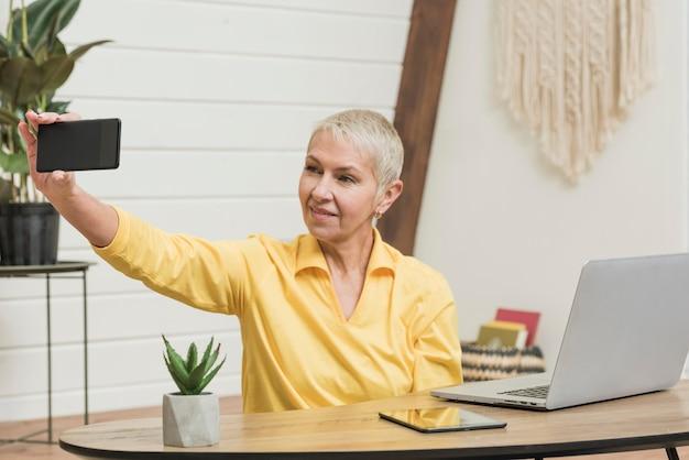 Smiley mulher sênior tomando uma selfie Foto gratuita