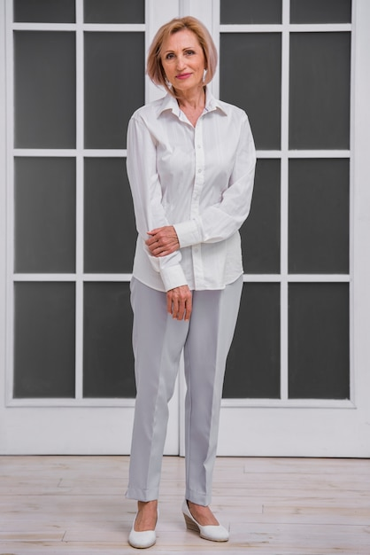 Smiley mulher sênior vestindo uma camisa branca Foto gratuita