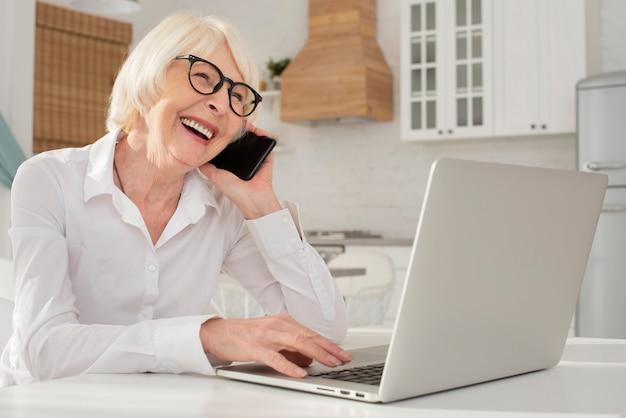 Smiley mulher sentada na cozinha Foto gratuita