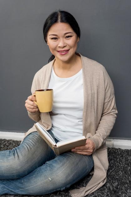 Smiley mulher tomando café e lendo Foto gratuita