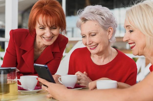Smiley mulheres olhando para um telefone Foto gratuita
