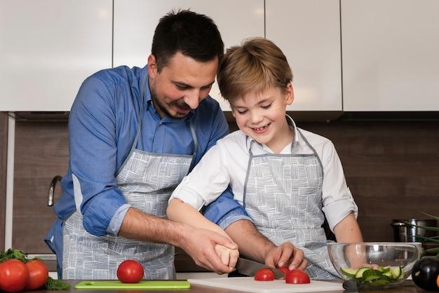 Smiley pai e filho cortar legumes Foto gratuita