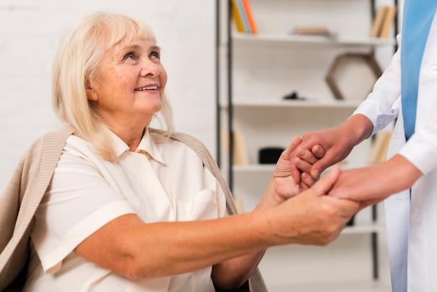 Smiley velha de mãos dadas com a enfermeira Foto gratuita