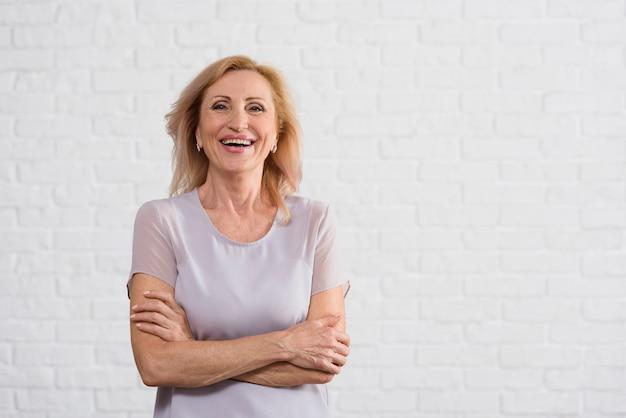 Smiley velha olhando para a câmera com fundo de tijolo Foto gratuita