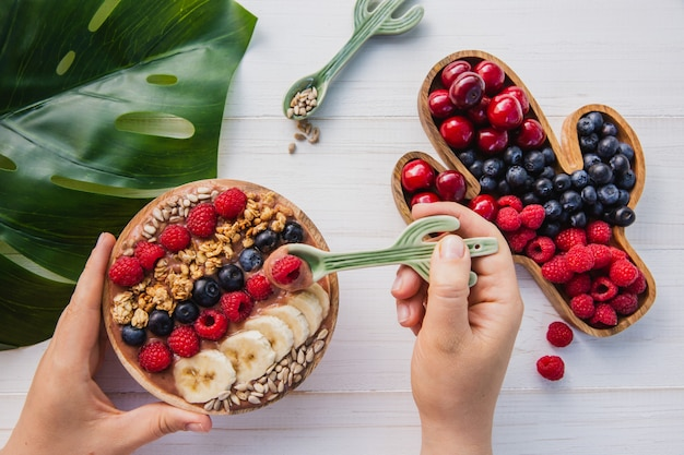 Smoothie de açaí, granola, sementes, frutas frescas em uma tigela de madeira nas mãos femininas com colher de cacto. prato cheio de bagas Foto Premium