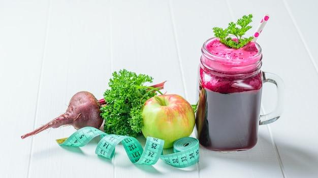 Smoothie de beterraba fresca, maçã, salsa e fita métrica na mesa de madeira branca. Foto Premium