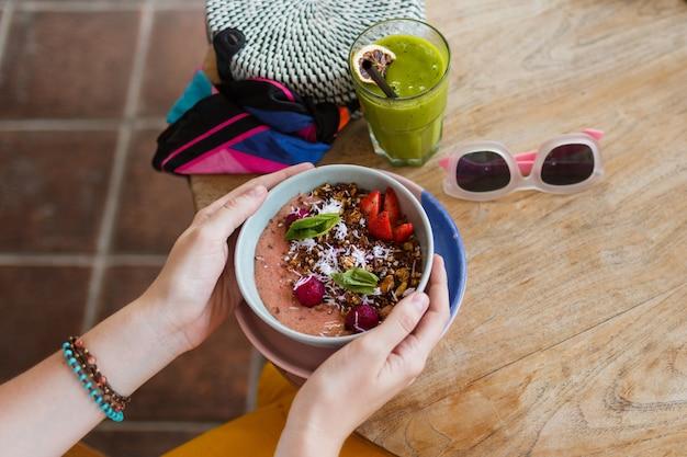 Smoothie de exploração de mulher. tigela de superalimentos coberta com chia, granola e abacate. Foto gratuita