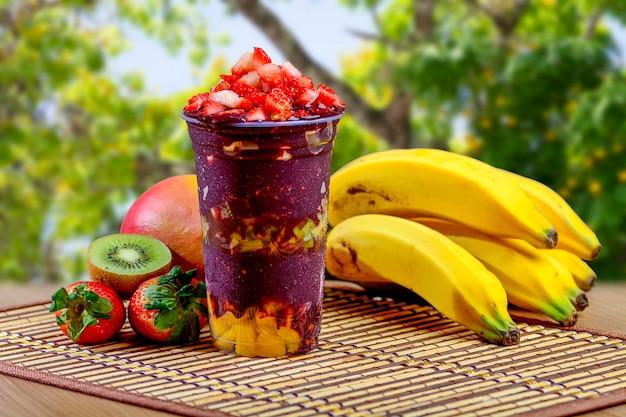 Smoothie de verão açaí com cobertura de morangos, banana, kiwi e granola Foto Premium