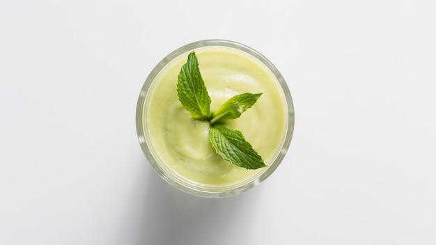 Smoothie de vista superior verde em vidro com hortelã Foto Premium