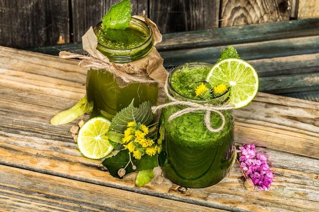 Smoothie verde em uma jarra com limão, kiwi e frutas vermelhas Foto gratuita