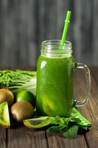 Smoothie verde misturado com ingredientes na mesa de madeira Foto Premium