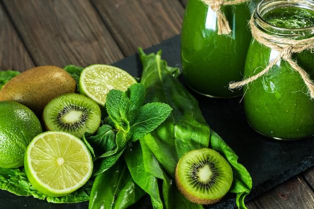 Smoothie verde misturado com ingredientes na placa de pedra, mesa de madeira Foto Premium