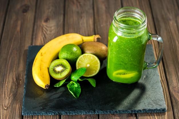 Smoothie verde misturado com ingredientes sobre o foco seletivo da mesa de madeira de pedra Foto Premium