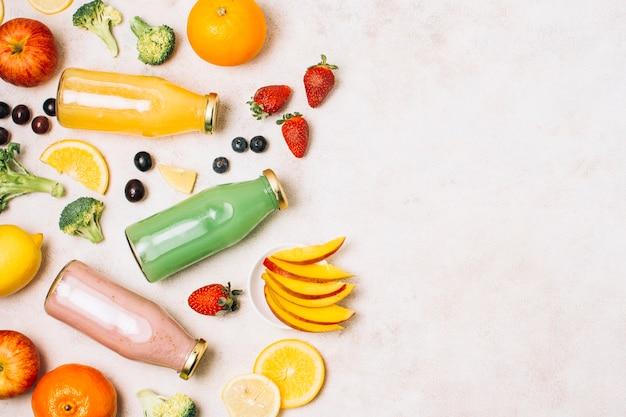 Smoothies coloridos planos e frutas com cópia espaço Foto gratuita