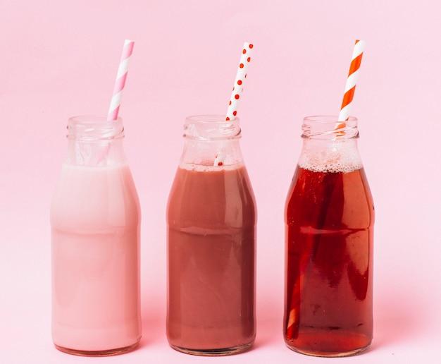 Smoothies de vista frontal rosa e vermelho Foto gratuita
