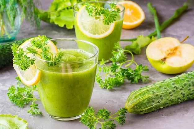 Smoothies refrescantes de pepino, maçã verde, ervas frescas e suco de limão em copos transparentes em cima da mesa. o conceito de uma dieta saudável. menu vegetariano Foto Premium