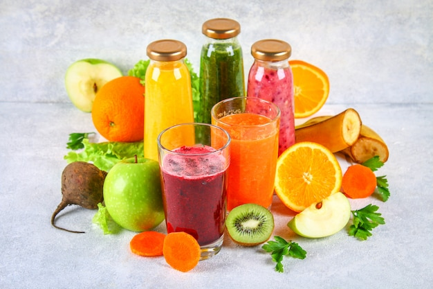 Smoothies verdes, amarelos, roxos em garrafas de groselha, salsa, maçã, kiwi, laranja, sobre uma mesa cinza. Foto Premium